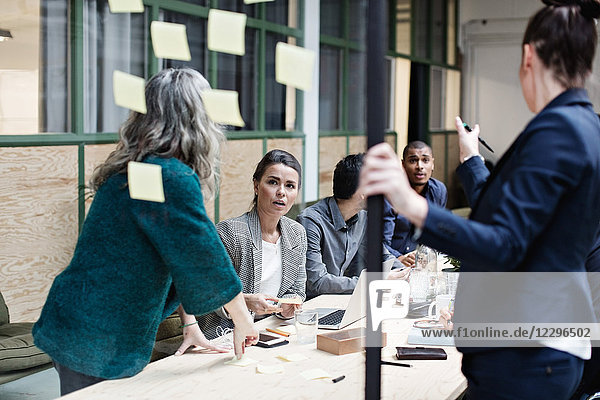 Female professionals discussing over adhesive notes with colleagues in meeting at office