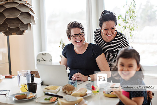 Cheerful mothers looking at daughter having breakfast on dining table
