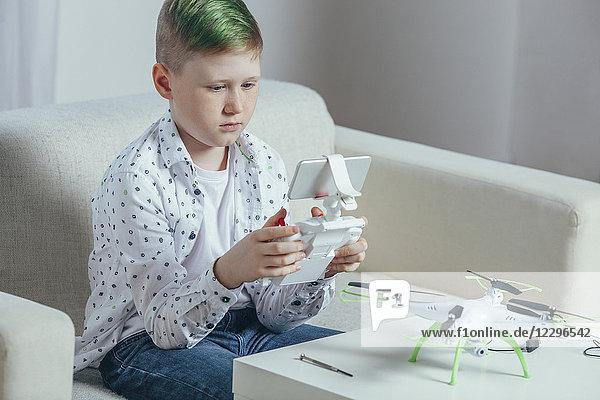 Junge mit Fernbedienung sitzend auf dem Sofa per Drohne auf dem Couchtisch zu Hause