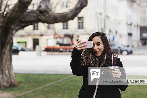 Glückliche Frau fotografiert vom Smartphone aus  während sie in der Stadt einen Drink hält.