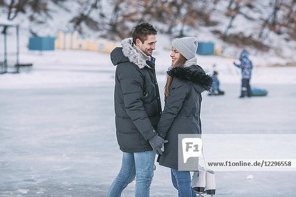 Glückliches Paar steht auf der Eisbahn