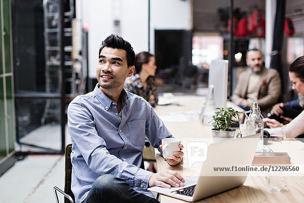 Smiling businessman having coffee and using laptop while sitting with colleagues at table