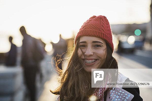 Porträt einer lächelnden mittleren erwachsenen Frau mit Strickmütze am Himmel bei Sonnenuntergang