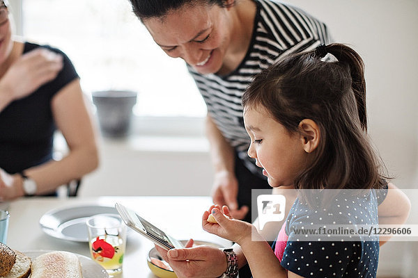 Smiling mother showing mobile phone to daughter while sitting with woman at dining table
