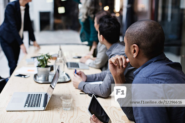 Business colleagues listening while sitting at table during meeting