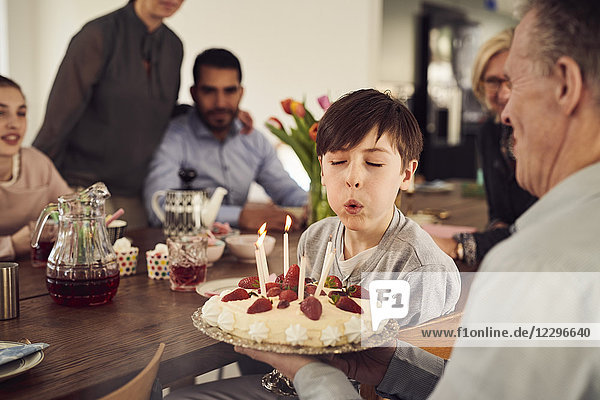 Boy blowing candles on birthday cake while enjoying in party with family at home