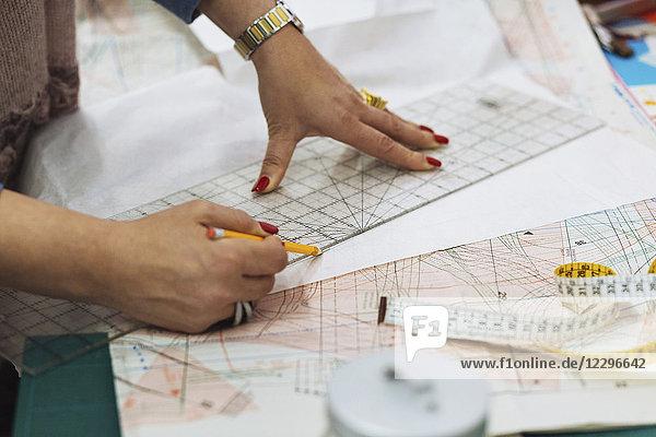 Beschnittenes Bild der Modedesigner-Markierung auf dem Stoff in der Werkstatt