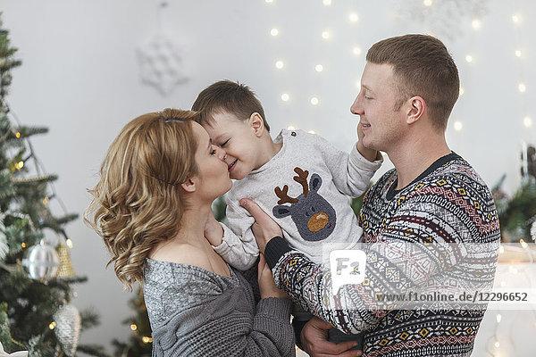 Vater und Mutter mit Sohn zu Hause zu Weihnachten
