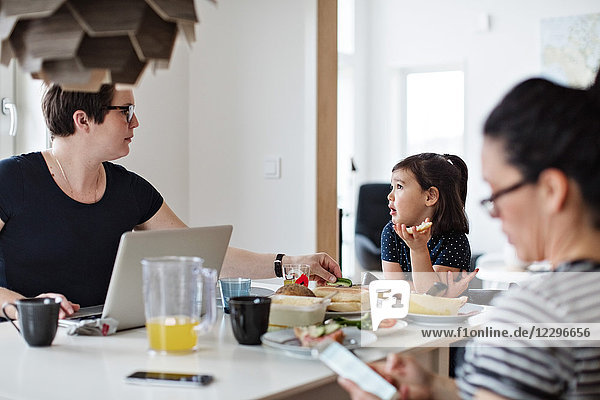 Mother with laptop talking to daughter while woman using phone at dining table