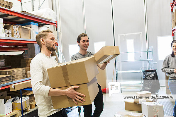 Woman looking at coworkers carrying boxes in distribution warehouse