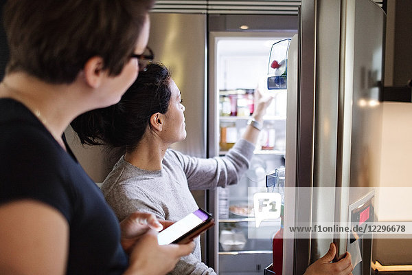 Woman with mobile phone looking at girlfriend opening refrigerator in kitchen