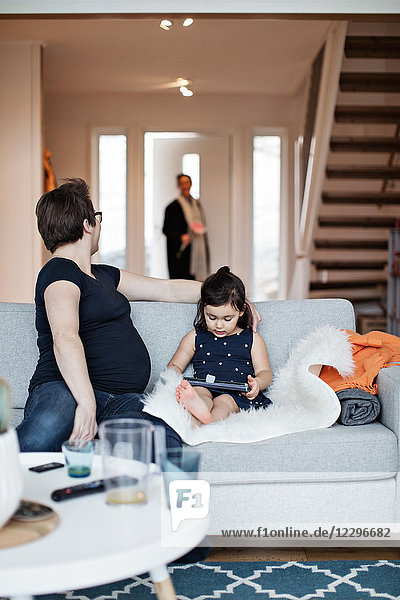 Mother sitting with daughter on sofa looking at woman entering house
