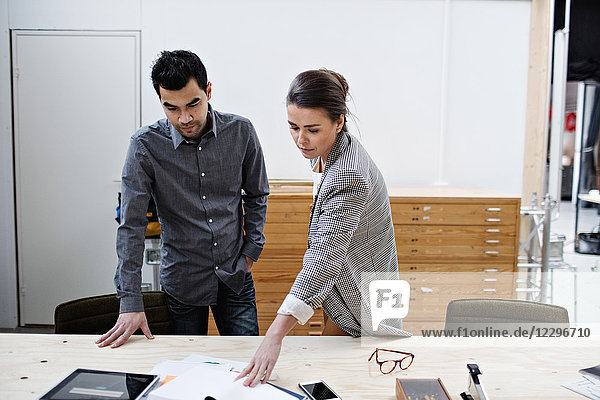 Confident male and female business colleagues discussing over documents at table in office