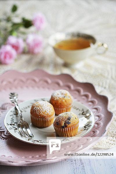 Kleine Muffins auf Teller mit Gabel  Teetasse und Blumen
