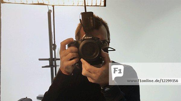 Photographer Looking Through Flashing Camera Lens