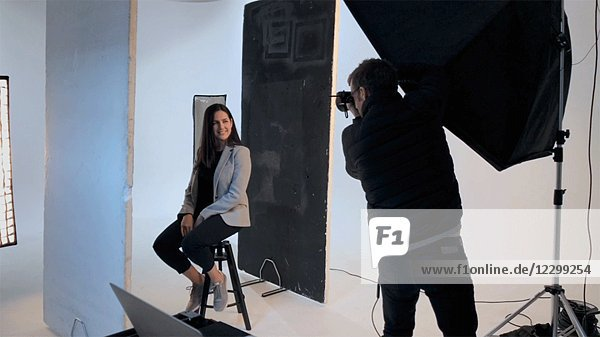 Photographer Shooting Portrait of Young Adult Woman in Photo Studio