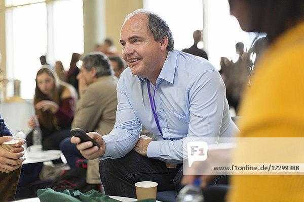 Smiling businessman using smart phone at conference Smiling businessman using smart phone at conference