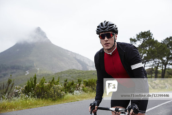 Portrait confident  determined male cyclist cycling on road