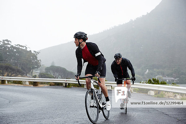 Dedicated male cyclists cycling on wet road