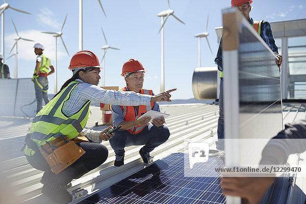 Female engineers talking  examining solar panels at power plant