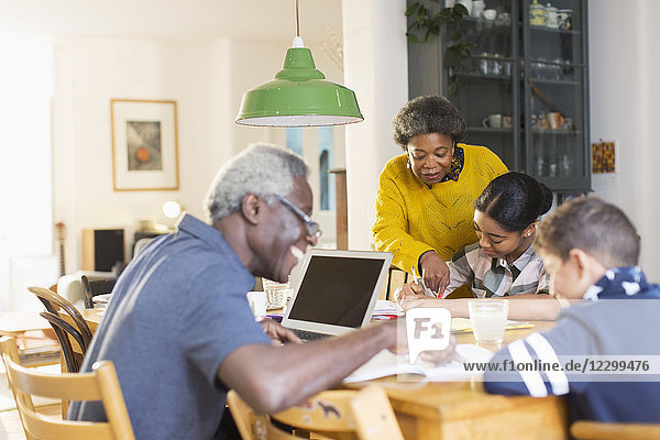 Grandparents helping grandchildren with homework at dining table