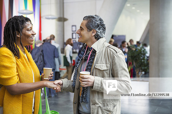 Businessman and businesswoman networking  handshaking at conference