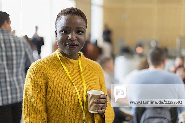 Portrait confident businesswoman drinking coffee at conference Portrait confident businesswoman drinking coffee at conference