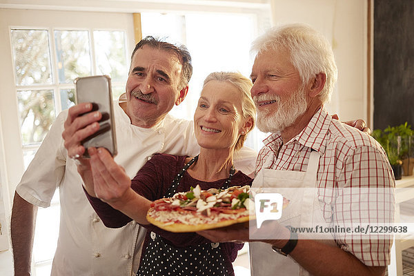 Chef and senior couple taking selfie with pizza in cooking class