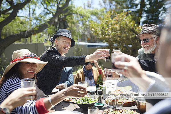 Happy senior friends toasting wine glasses at sunny garden party table