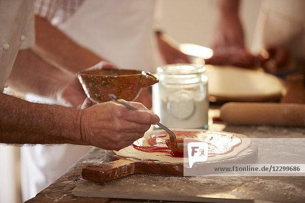 Close up man spreading marinara sauce on dough in pizza cooking class