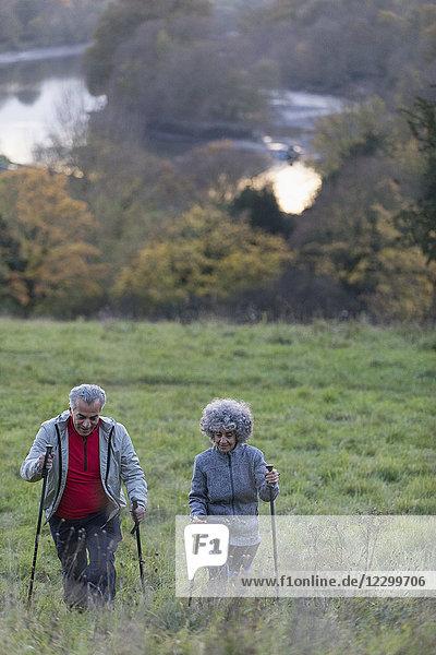 Active senior couple hiking up rural hillside