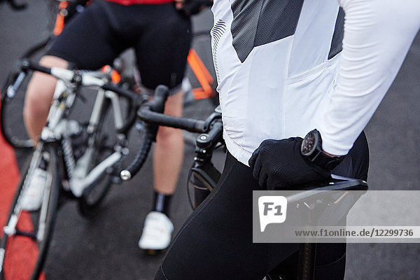 Close up male cyclist resting on bicycle