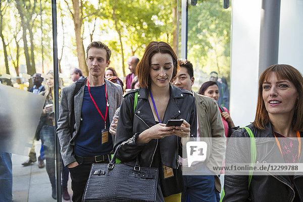 Businesswoman with smart phone arriving  entering doorway Businesswoman with smart phone arriving, entering doorway