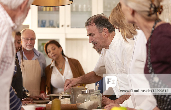 Chef explaining to active senior friends in cooking class