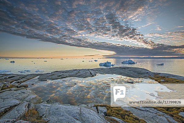 Idyllic clouds over remote ocean with icebergs  Kalaallisut  Greenland