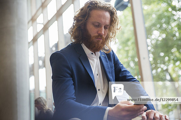 Businessman texting with smart phone in office lobby Businessman texting with smart phone in office lobby