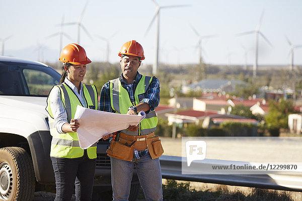Engineers reviewing blueprints near wind turbine farm