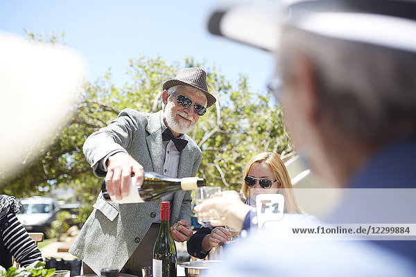 Senior man in suit and bow tie pouring wine for friends at sunny garden party