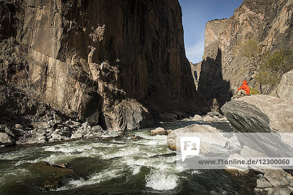 Hiker sitting on rock over river at bottom of Black Canyon  Colorado  USA