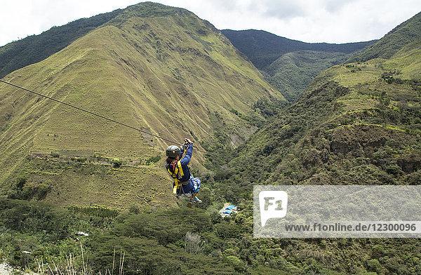 Adventurous woman riding on zipline through Amazon forest  Santa Teresa  Cusco region  Peru