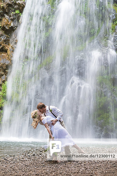 Bride and groom creative portrait at the base of Fall Creek Falls a waterfall in the North Umpqua National Forest in Oregon during an elopement style wedding.