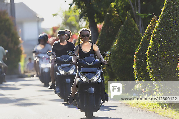 Front view of young woman leading line of people on motorbikes