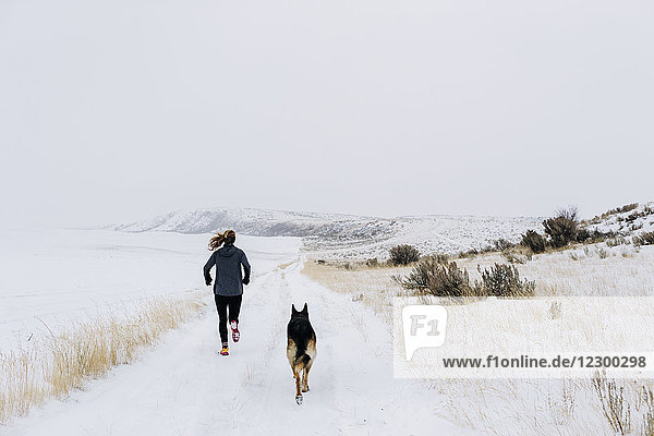 A young female athlete and her dog trail run on a foggy winter morning.