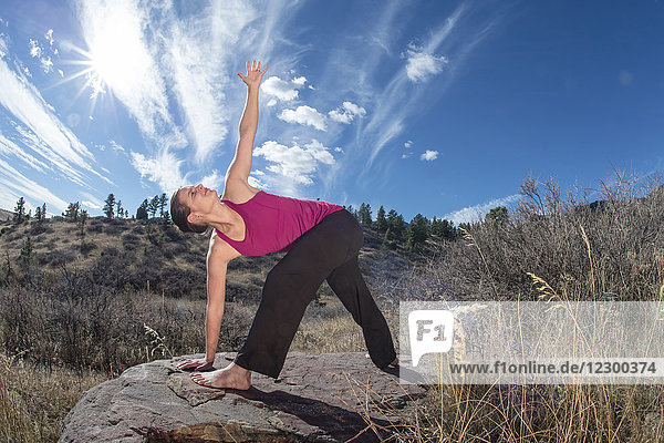 Sun shining over adult woman stretching barefoot on rock surrounded by grasses  Boulder  Colorado  USA