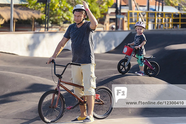 Father with son with BMX bikes at skate park