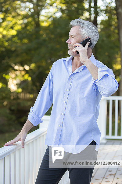 Gray-haired man making phone call while standing outdoors on porch  Orleans  Massachusetts  USA