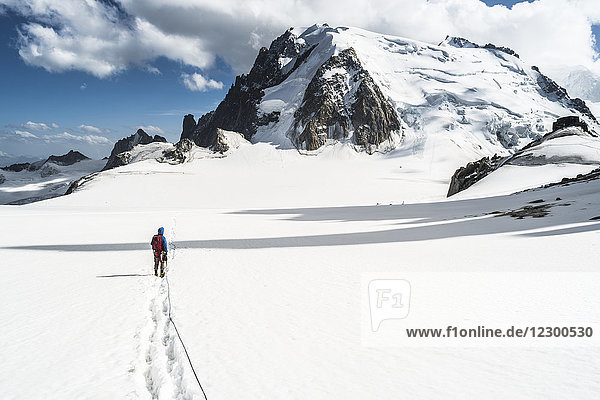 Mountaineer crossing snowcapped terrain in front of Mont Blanc du Tacul  Haute-Savoie  France
