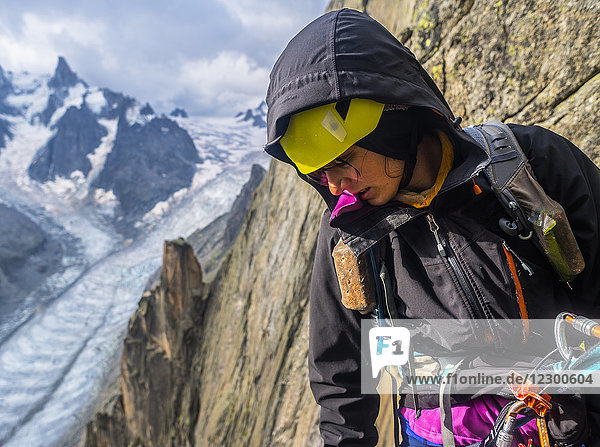 Waist up shot of female rock climber in hooded jacket looking down in French Alps  Aiguille du Grepon  Haute-Savoie  France