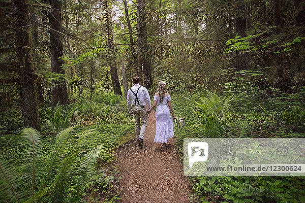 Bride and groom hike together on a hiking trail to Fall Creek Falls in the North Umpqua National Forest of Oregon.