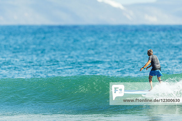 A man surfing a longboard on a wave on a sunny day at TeaTree Point in Noosa National Park.
